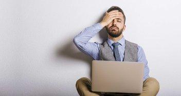 Ein Mann sitzt vor seinem Laptop und hält sich mit seiner rechten Hand die Stirn.