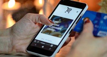 Eine Frau öffnet auf ihrem Smartphone einen Online-Shop. In der rechten Hand hält sie ihre Kreditkarte für die Zahlung bereit.