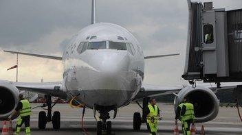 Flugzeug vom Typ Boeing steht am Gate und wird vom Bodenpersonal abgefertigt.