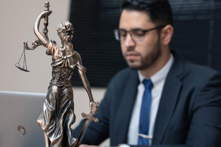 Ein Mann im Anzug zeigt mit einer Banane Richtung Kamera