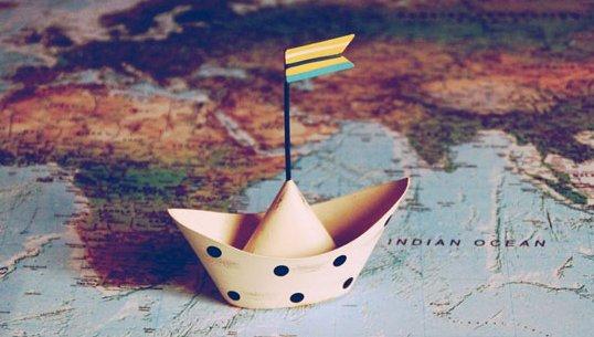 Ein Papierboot auf einer Weltkarte.