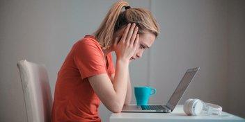 Frau sitzt traurig am Tisch, vor dem PC.