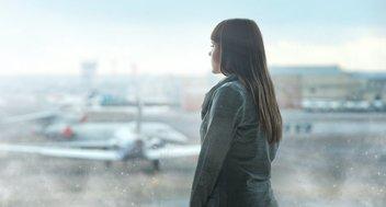 Frau wartet am Flughafen und schaut auf Flugzeuge