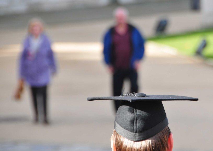 Die Rückansicht eines Studierenden. Auf dem Kopf trägt er einen Bachelor-Hut. Im Hintergrund sind zwei Personen auf einem Platz zu sehen.