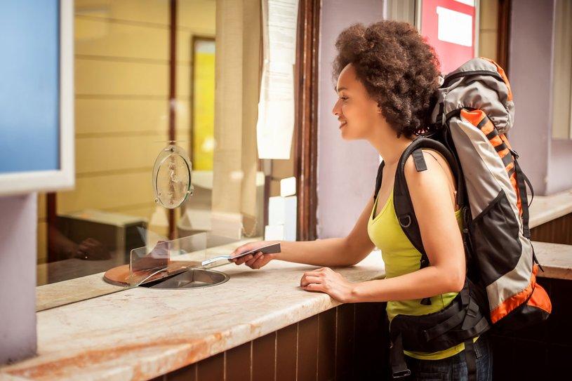 Eine junge Frau kauft einen Fahrschein an einem Schalter.
