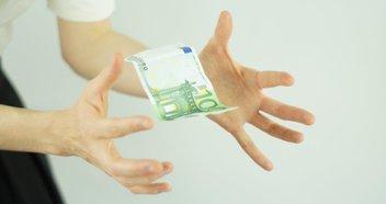 Hände wollen Geldschein ergreifen