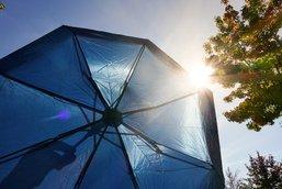 Blauer Regenschirm vor sonnigem Himmel