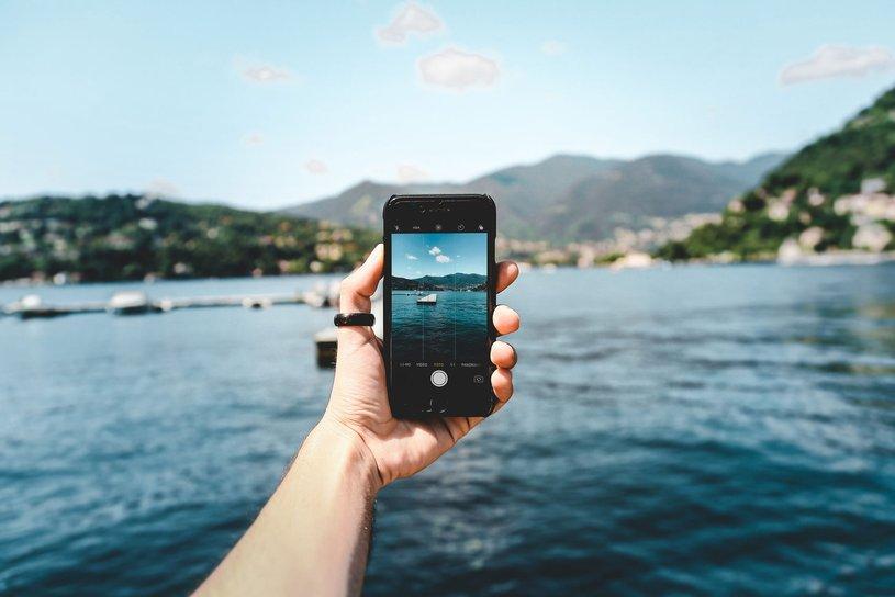 Eine Person macht mit ihrem Smartphone ein Foto vom Meer.
