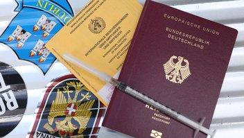 Ein Impfausweis und ein deutscher Reisepass liegen auf einem Gepäckkoffer.
