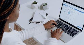Frau sitzt vor dem Laptop, hat Facebook-Seite geöffnet