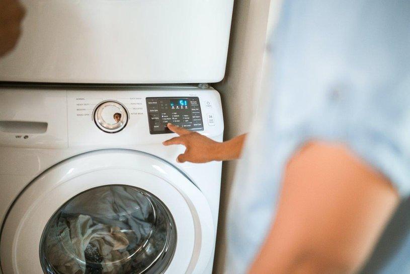 Mann betätigt Waschmaschine