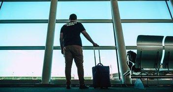 Mann steht im Flughafengebäude und schaut aus dem Fenster.