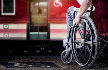 Eine Person sitzt in einem Rollstuhl am Bahngleis und wartet auf den Zug.
