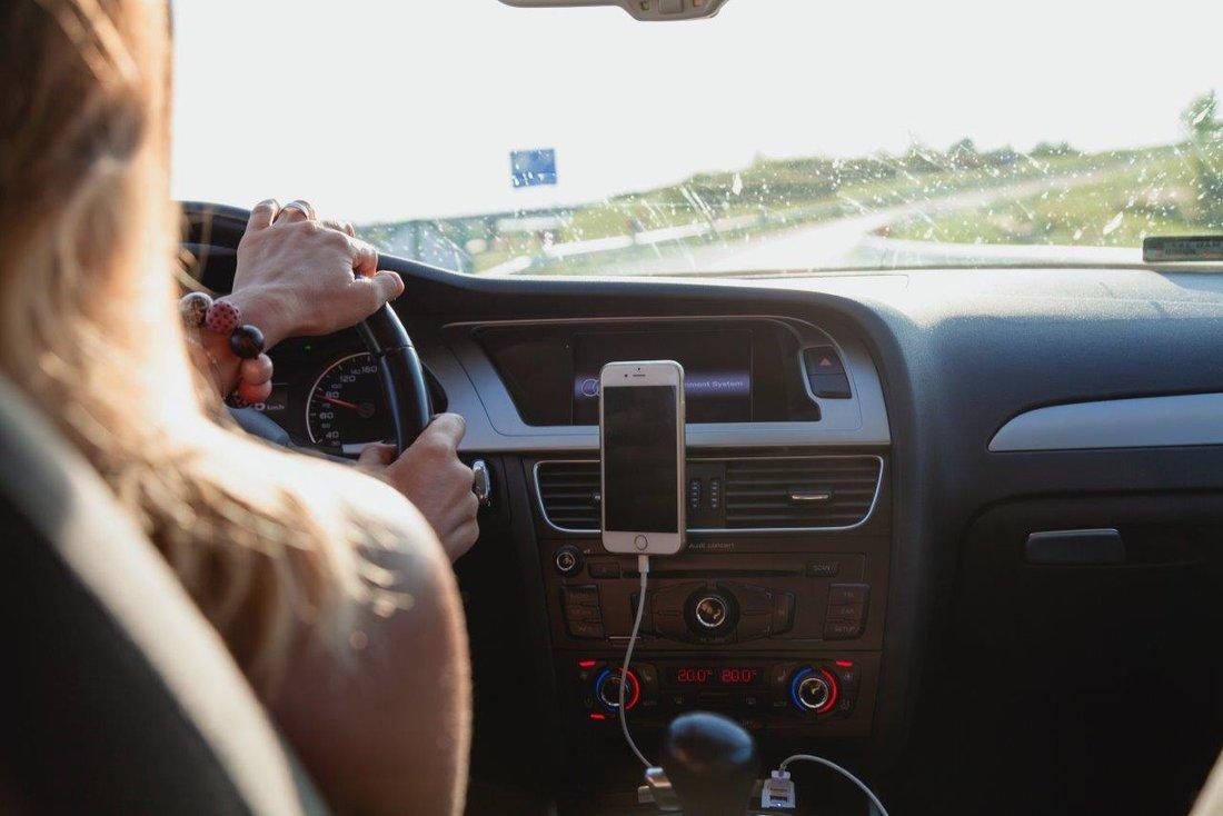 Frau fährt im Auto, Hand am Steuer